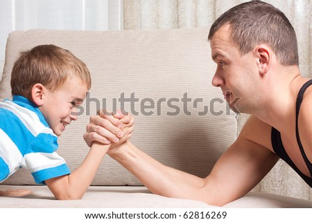 Father and young son are fighting, indoor - stock photo
