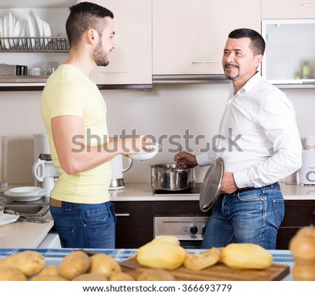 father and young son cooking potato soup indoors. Focus on the right man