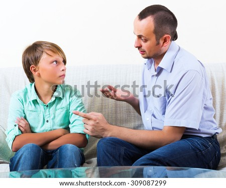 Father and young son discussing something serious in living room - stock photo