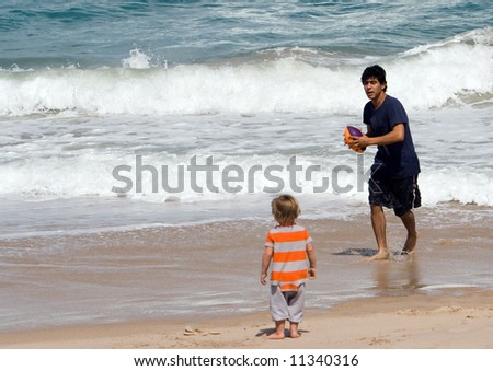 Father and young son on beach playing near waves with a football - stock photo