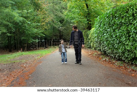 father and young son walking in a park - stock photo