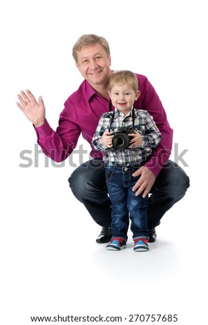 Father and young son with a camera in the studio isolate on white background. - stock photo