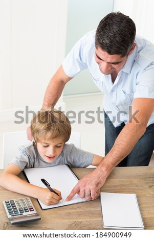 Father assisting boy in solving maths at home