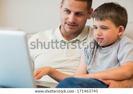 Father assisting boy in using laptop at home - stock photo