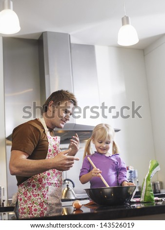 Father assisting daughter to prepare food in kitchen - stock photo