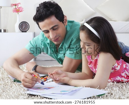 Father assisting girl in drawing while lying on rug at home - stock photo