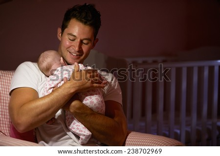 Father At Home Cuddling Newborn Baby In Nursery - stock photo