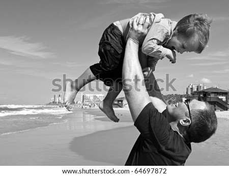 father at the beach with his son - stock photo