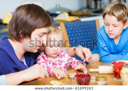 Father baking together with his two kids - stock photo