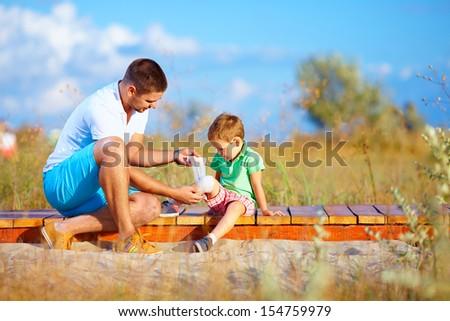 father bandaging injured leg of kid - stock photo