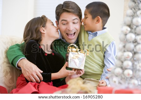 Father Being Given A Christmas Present By His Daughter And Son - stock photo