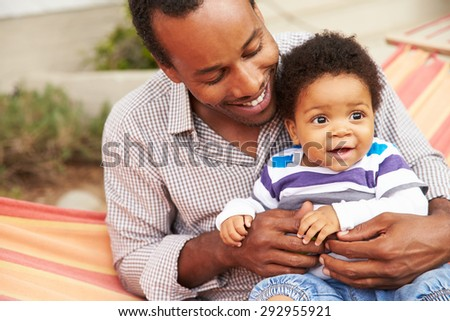 Father bonding with young son sitting in a hammock - stock photo