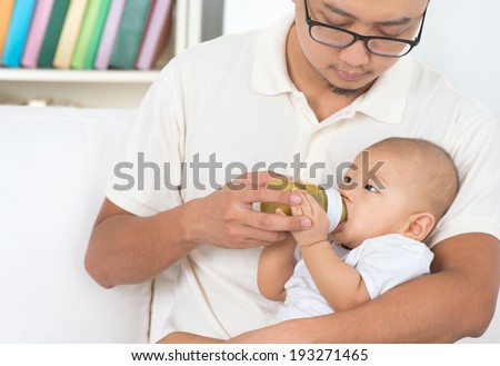 Father bottle feeding baby fruits puree. Asian family lifestyle at home. - stock photo