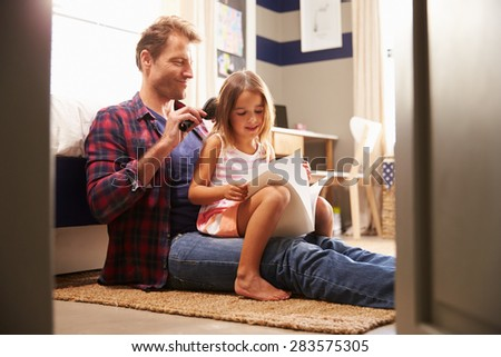 Father brushing young daughter's hair - stock photo