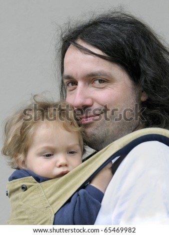 Father carries his one year old son in stylish sling baby carrier - stock photo