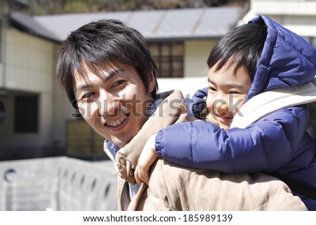 father carrying boy on his back