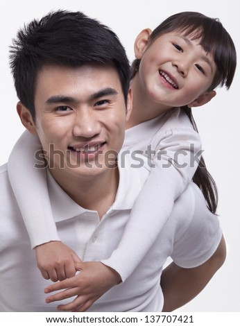 Father carrying daughter on back, studio shot - stock photo