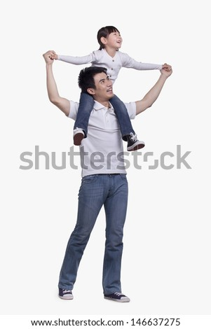 Father carrying daughter on his shoulders, studio shot - stock photo