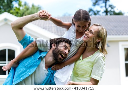 Father carrying daughter on shoulder besides woman in yard - stock photo