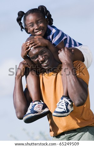 Father carrying his daughter on his shoulders - stock photo