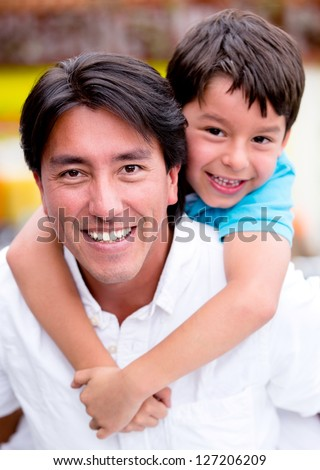 Father carrying his son at the back looking happy - stock photo