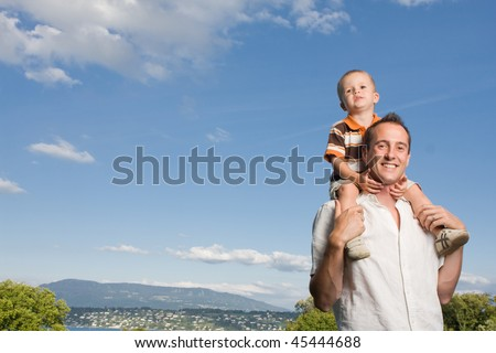 Father carrying his son on piggy back ride outdoors against nature and blue sky - stock photo