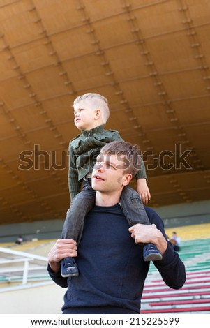 Father carrying his son on shoulders outdoor   - stock photo