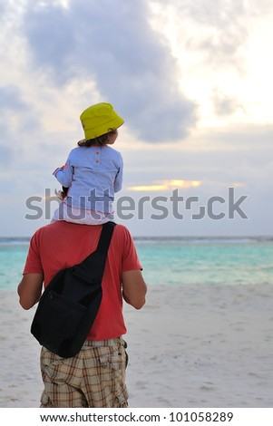 Father carrying on shoulders his little girl - stock photo