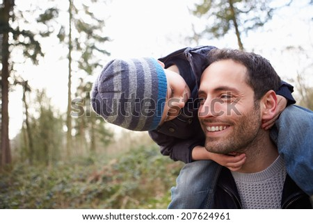Father Carrying Son On Shoulders During Countryside Walk - stock photo