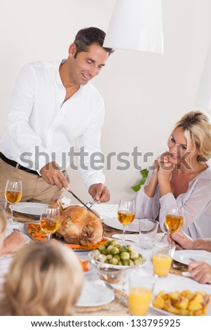 Father carving the turkey at the head of table at thanksgiving - stock photo