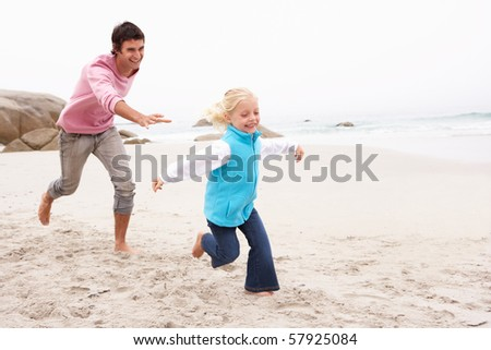 Father Chasing Daughter Along Winter Beach