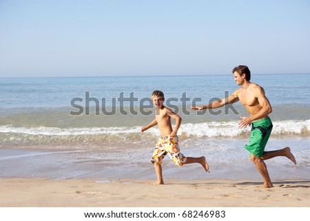 Father chasing young boy on beach - stock photo