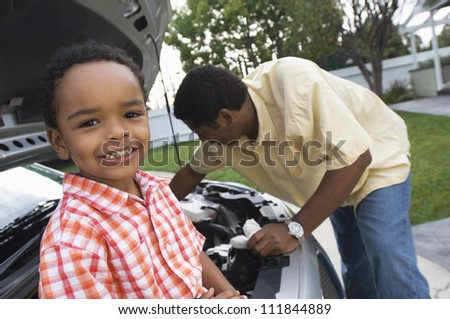 Father checking oil level with his son - stock photo