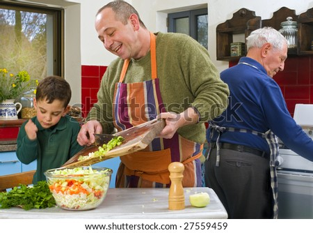 father child and grandfather cooking in the kitchen together - stock photo