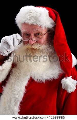 father christmas looking over spectacles studio shot on black - stock photo