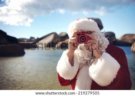 Father Christmas on a beach taking a picture with copyspace - stock photo