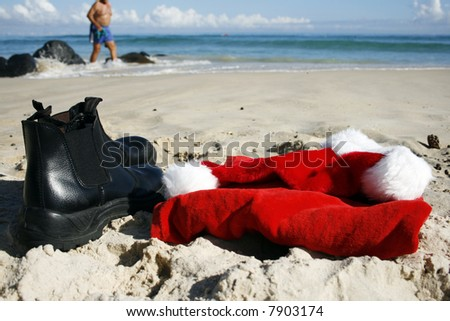 Father Christmas on Boxing Day at the beach, after the busiest night of the year, showing his hat, clothes and him walking  on the beach in his swimmers and the ocean in the background - stock photo