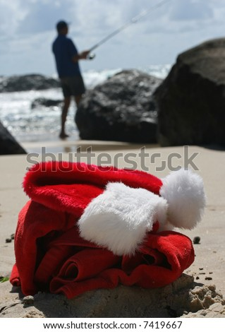 Father Christmas on Boxing Day relaxing fishing after the busiest night of the year, showing his hat, clothes and the ocean in the background - stock photo