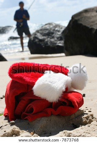 Father Christmas on Boxing Day relaxing fishing after the busiest night of the year, showing his hat, clothes and a festive cocktail resting on the rocks and the ocean in the background - stock photo