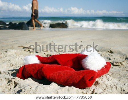 Father Christmas on Boxing Day relaxing walking on the beautiful beach, showing his hat, clothes  and the ocean in the background - stock photo