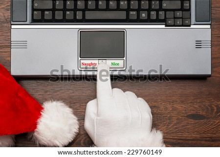 Father Christmas or Santa checking his list on a computer to select if a boy or girl is either Naughty or Nice. - stock photo