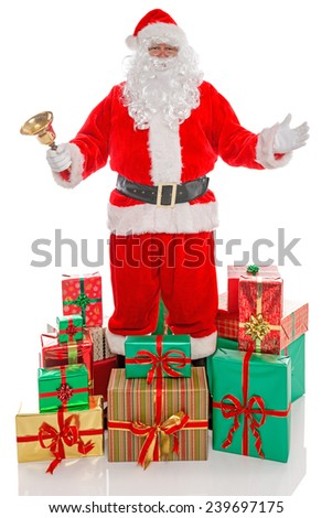 Father Christmas or Santa Claus holding a gold bell surrounded by piles of gift wrapped presents, isolated on a white background. - stock photo