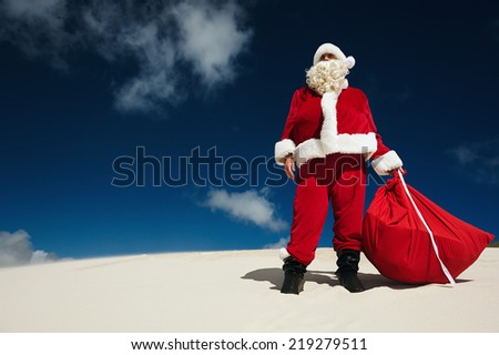 Father Christmas standing on a beach holding his sack full of presents - stock photo