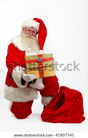 father christmas taking a gift box from his sack - stock photo