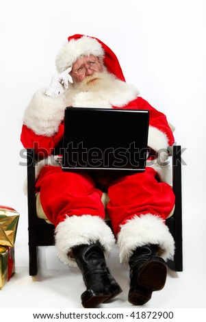 father christmas using laptop and thinking - stock photo
