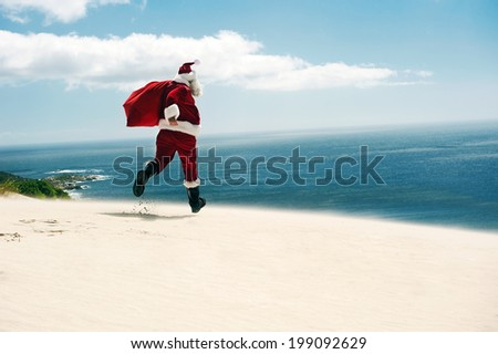 Father Christmas walking along the beach with copyspace - stock photo