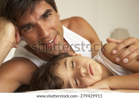 Father Comforting Sleeping Son In Bed - stock photo