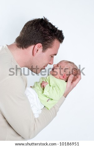 father connecting with his newborn baby son - stock photo