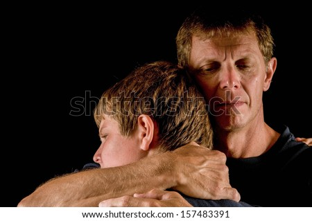 Father, crying, hugs teenage son - closeness, forgiveness, loss, transition, solace... - stock photo