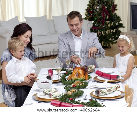 Father cutting a turkey in Christmas dinner for his family - stock photo